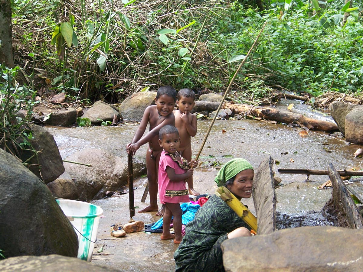 Children enjoying their shower in a small stream amid the greens of our estate